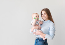 Happy Mother With Cute Little Baby On Light Background