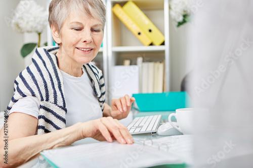 obraz dibond Seniorin als Geschäftsfrau macht Buchhaltung