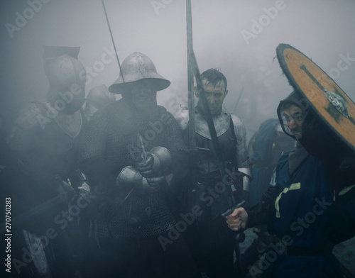 Foto  Combat squad of medieval knights of the Crusaders stand in armors preparing to attack in misty morning