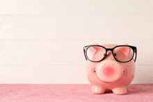 Happy Piggy Bank With Glasses On Color Table Against White Wooden Background, Space For Text. Finance, Saving Money