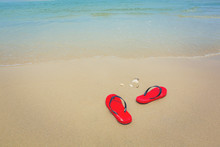 Red Flip Flops On A Sandy Ocean Beach With Seashell, Coral