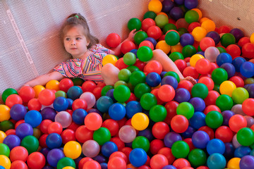 Fototapeta na wymiar Little girl playing with colorful plastic balls on the playground. Top view