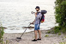 Man With A Metal Detector On The Shore Of A Sandy Beach.