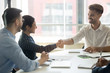 Smiling diverse partners handshake collaborating at office meeting