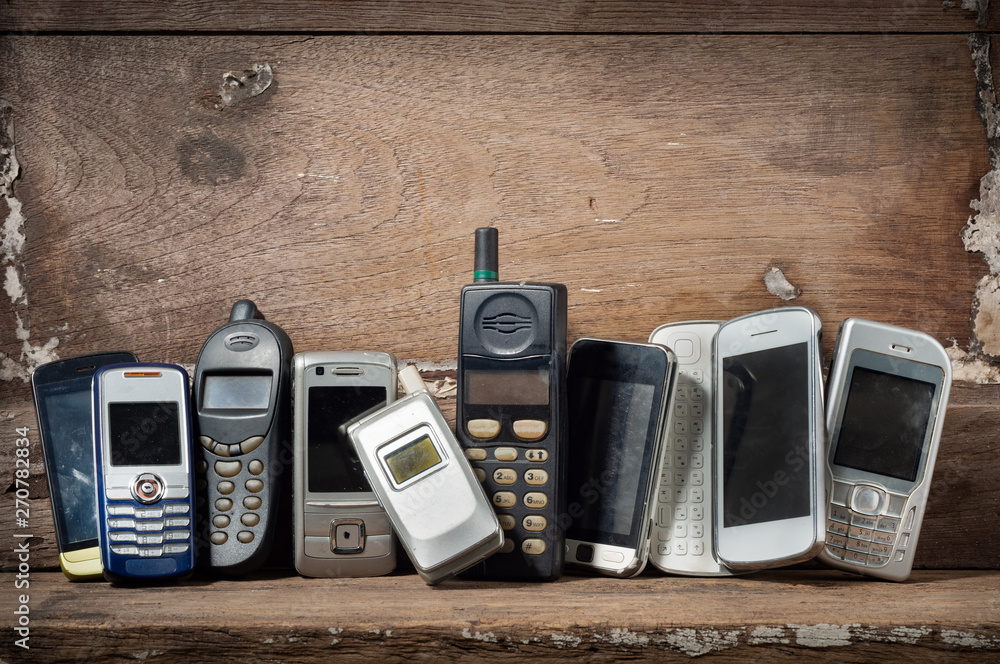 Fototapety, obrazy: Old and obsolete mobile phone or cell phones on space of old wood background