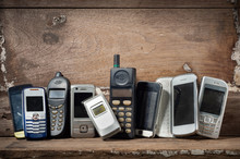 Old And Obsolete Mobile Phone Or Cell Phones On Space Of Old Wood Background