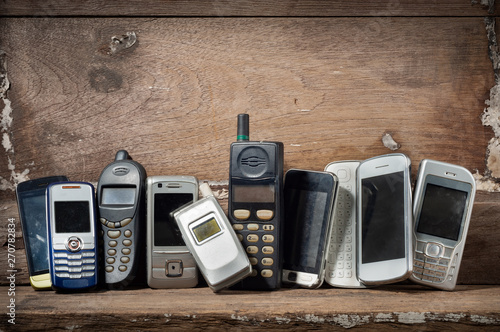 Obraz Old and obsolete mobile phone or cell phones on space of old wood background - fototapety do salonu