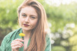 Frau, jung, 20-30, lächelnd, romantisch, genießt die ersten Sonnenstrahlen im Frühling und hält einen Löwenzahn in der Hand.