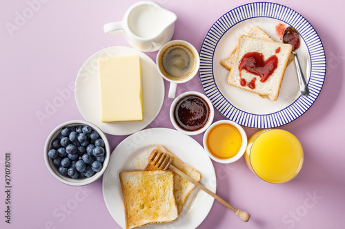 Photo  top view of served breakfast with cup of coffee and orange juice on violet backg