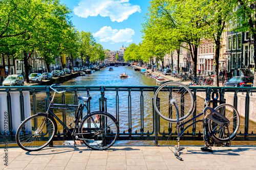 Photo  Old bicycle on the bridge in Amsterdam, Netherlands against a canal during summer sunny day