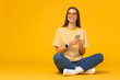 canvas print picture - Happy young girl sitting on the floor, holding smartphone in hands and looking away, isolated on yellow background with copy space