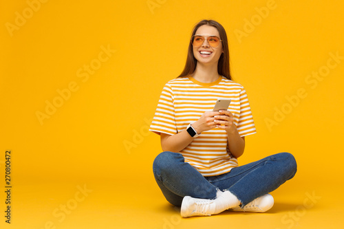 Fotomural  Happy young girl sitting on the floor, holding smartphone in hands and looking a