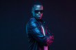 canvas print picture - Studio neon portrait of stylish black man standing with crossed arms, wearing leather jacket and sunglasses
