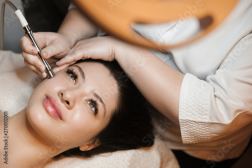 Fotografía  Upper view portrait of a beautiful caucasian female leaning on a bed with eyes open while having non invasive microdermabrasion on her face in a spa salon