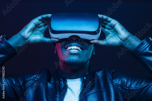Obraz African man wearing virtual reality headset having great fun - fototapety do salonu