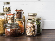 Various Cereals And Seeds - Peas Split, Pumpkin Seeds, Beans, Rice, Pasta, Oatmeal, Couscous, Flax, Lentils, Almond Slices, Bulgur In Glass Jars On The Table In The Kitchen