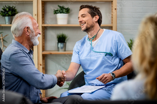 Happy doctor and mature man handshaking while greeting during a home visit Fototapeta