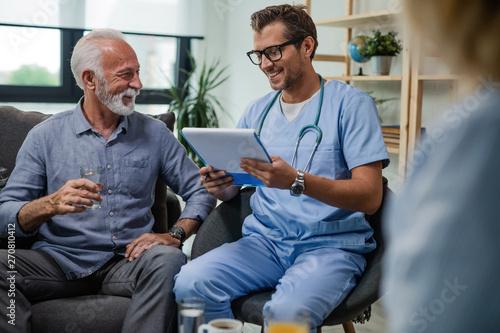 Happy doctor reading medical documents while visiting senior patient at home Fototapet