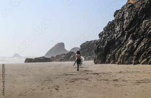 Valokuva  Young man surfer with no shirt and bushy long dark hair walks down misty beach w