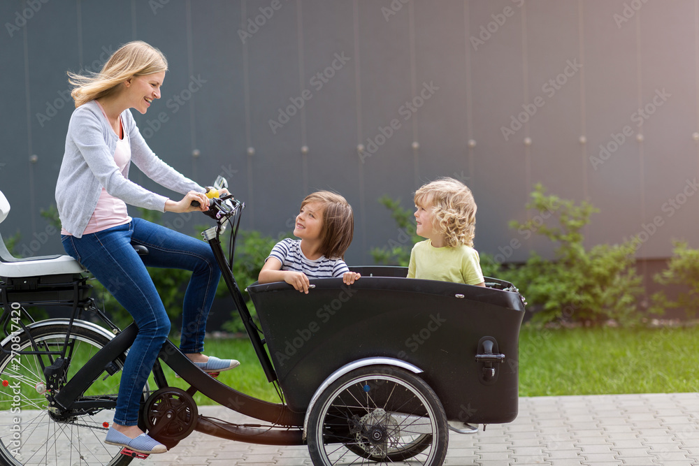 Fototapety, obrazy: Mother and children having a ride with cargo bike