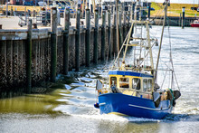 A Small Fishing Boat Enters The Harbour Of Büsum In North Frisia In Germany
