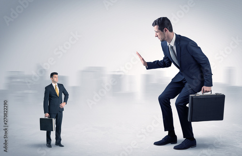 Photo Giant businessman being afraid of small serious executor with suitcase