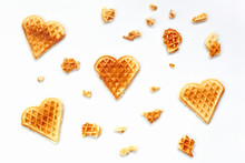 Background From Heart Shaped Waffles And Pieces Of Waffle On White Backdrop. Concept Love For Sweet