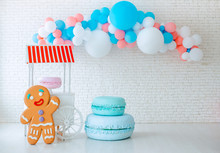 Balloons And Ice Cream Cart On Festive White Brick Background With Big Gingerbread Man.