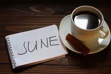 June Inscription And Word In A Notebook Near A Cup Of Coffee