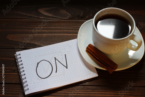 on inscription and word in a notebook near a cup of coffee Wallpaper Mural