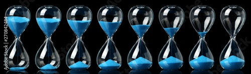 Leinwand Poster Collection of hourglasses with blue sand showing the passage of time