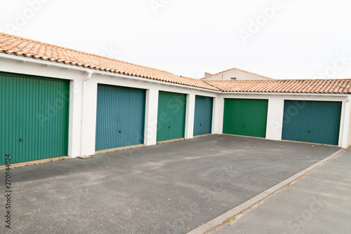 Fototapeta Row of parking garages car with green doors