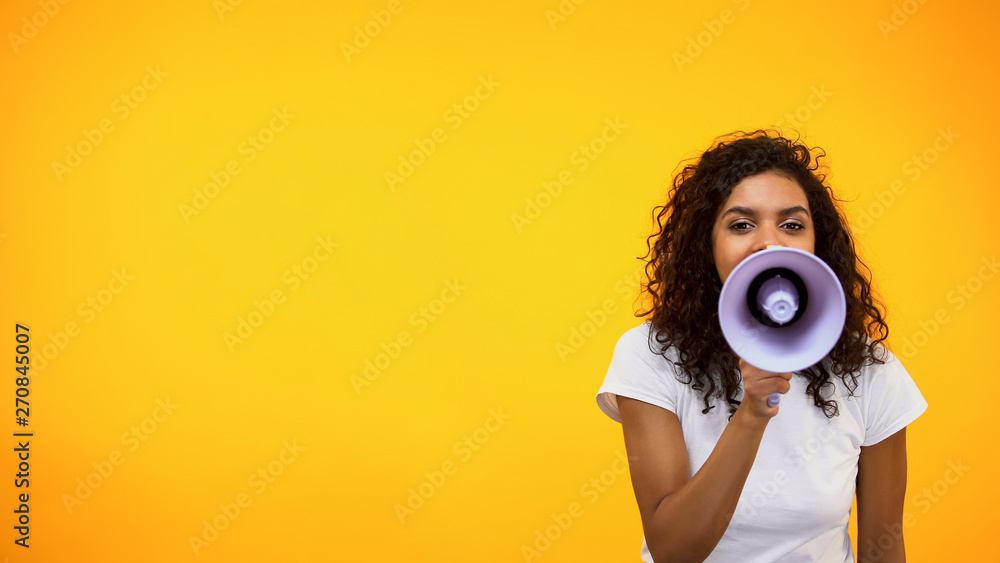 Fototapeta Afro-American female shouting in megaphone, public relations, social opinion