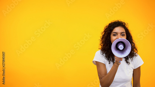 Tela Afro-American female shouting in megaphone, public relations, social opinion
