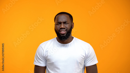 Photo  Displeased African-American man looking at camera isolated on yellow background