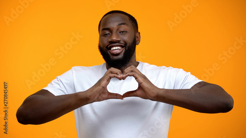 Afro-American man in love showing heart gesture, happy relations, acquaintance Canvas Print