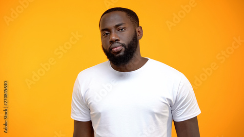 Fotografie, Obraz  Upset African-American man looking at camera isolated on yellow background