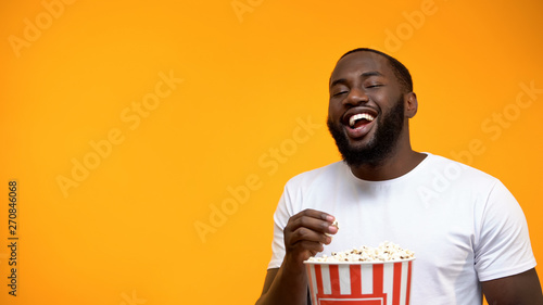 Cheerful Afro-American man eating popcorn and laughing out loud, comedy show Fototapeta