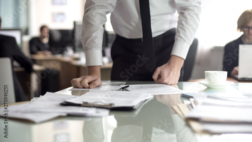 Fototapeta  Dissatisfied ceo reading contract, leaning on table with anger, error report