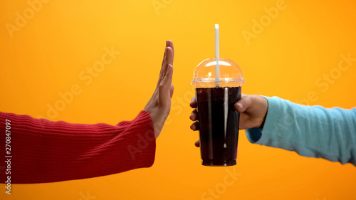 Valokuva  Lady showing stop gesture to soft drink on bright background, sugar overweight
