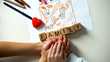 Kid Holding Hand Of Adult Person, Family Word Made From Cubes On House Picture