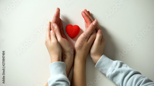 Red heart in child and mothers hands on white background, adoption concept Canvas Print