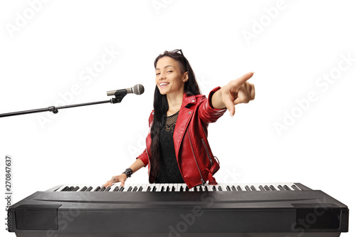 Young female musician playing a digital piano, singing on a microphone and point Canvas-taulu