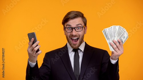 Photographie  Male looking at smartphone and immediately receiving money cash back application