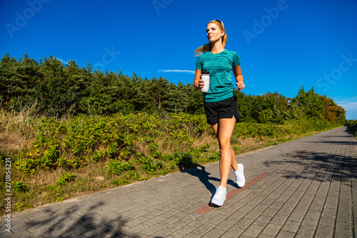 fototapeta na drzwi i meble Young woman running in city park