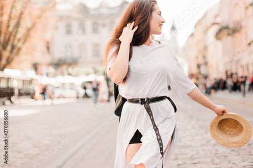 obraz PCV Young stylish woman walking on the old town street, travel with backpack, straw hat, wearing trendy outfit.