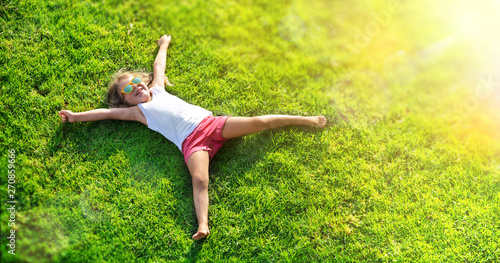 Poster Echelle de hauteur Smiling Little Girl Lying On Grass Meadow