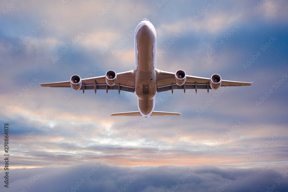 Leinwandbild Motiv - Lukas Gojda : Commercial airplane jetliner flying above dramatic clouds in beautiful sunset light. Travel concept.
