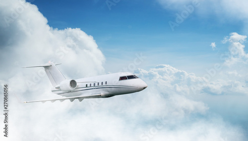 Foto Small private jetplane flying above beautiful clouds