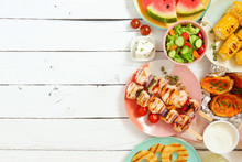 Summer BBQ Or Picnic Food Side Border. Selection Of Grilled Meat, Fruits, Salad And Potatoes. Top View Over A White Wood Background. Copy Space.